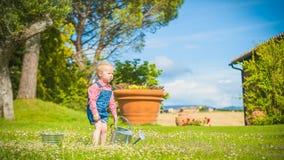 Piccolo assistente sull'erba verde nel giorno di estate rustico Immagini Stock Libere da Diritti
