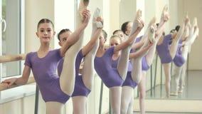 Piccolo ballerine che fanno allungando gli esercizi alla sbarra archivi video