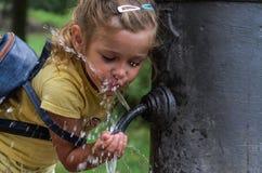 """Piccolo bambino adorabile della ragazza beve l'acqua dalla fontanella """"naso romano """" immagini stock libere da diritti"""