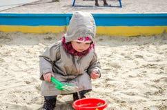Piccolo bambino adorabile della ragazza che gioca nella sabbiera sul campo da giuoco con una pala e un secchio che scavano un for Fotografie Stock