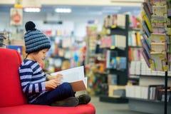 Piccolo bambino adorabile, ragazzo, sedentesi in un deposito di libro fotografia stock