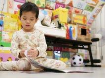 Piccolo bambino asiatico che apre e che esplora un libro fotografia stock