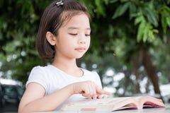 Piccolo bambino asiatico che legge un libro Fotografie Stock Libere da Diritti
