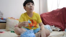 Piccolo bambino asiatico che mangia alimento dolce archivi video