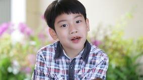 Piccolo bambino asiatico che mangia l'alimento del dolce della ciambella archivi video