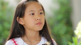 Piccolo bambino asiatico che mangia l'alimento del dolce della ciambella video d archivio