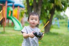 Piccolo bambino asiatico che tiene un Han di controllo telecomandato radiofonico immagini stock