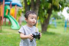 Piccolo bambino asiatico che tiene un Han di controllo telecomandato radiofonico fotografia stock
