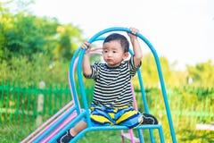 Piccolo bambino asiatico triste che si siede sullo scorrevole al campo da giuoco alla d immagini stock libere da diritti