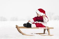 Piccolo bambino in attrezzatura del Babbo Natale nella neve Fotografie Stock Libere da Diritti