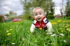 Piccolo bambino biondo adorabile con gli occhi azzurri che mette sull'erba Fotografia Stock Libera da Diritti