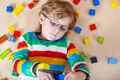 Piccolo bambino biondo che gioca con i lotti dei blocchi di plastica variopinti Fotografie Stock