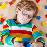 Piccolo bambino biondo che gioca con i lotti dei blocchi di plastica variopinti Fotografia Stock Libera da Diritti