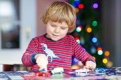 Piccolo bambino biondo che gioca con le automobili ed i giocattoli a casa Fotografia Stock Libera da Diritti