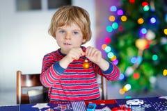 Piccolo bambino biondo che gioca con le automobili ed i giocattoli a casa Fotografia Stock