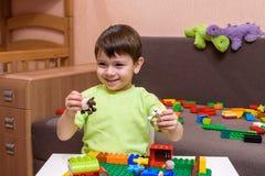 Piccolo bambino caucasico che gioca con i lotti dei blocchi di plastica variopinti dell'interno Scherzi la camicia d'uso del raga Fotografia Stock Libera da Diritti