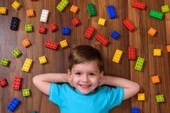 Piccolo bambino caucasico che gioca con i lotti dei blocchi di plastica variopinti dell'interno Scherzi la camicia d'uso del raga Fotografie Stock Libere da Diritti