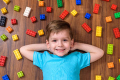 Piccolo bambino caucasico che gioca con i lotti dei blocchi di plastica variopinti dell'interno Scherzi la camicia d'uso del raga Immagine Stock
