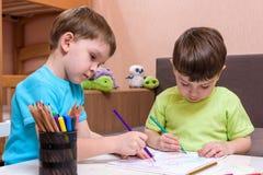 Piccolo bambino caucasico che gioca con i lotti dei blocchi di plastica variopinti dell'interno Scherzi la camicia d'uso del raga Immagini Stock