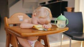 Piccolo bambino che dorme sul bambino del seggiolone dopo l'alimentazione video d archivio