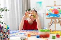 Piccolo bambino che fa cuore con le mani dipinte alla tavola fotografia stock