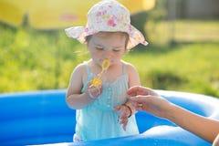Piccolo bambino che gioca con i giocattoli in stagno gonfiabile fotografia stock libera da diritti