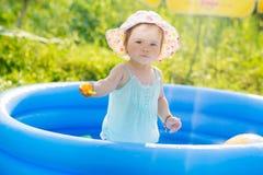 Piccolo bambino che gioca con i giocattoli in stagno gonfiabile immagini stock