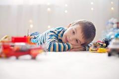 Piccolo bambino che gioca con i lotti dei giocattoli di plastica variopinti dell'interno Immagini Stock