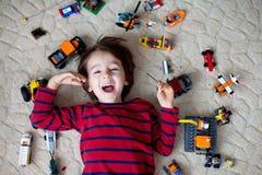 Piccolo bambino che gioca con i lotti dei giocattoli di plastica variopinti dell'interno Fotografia Stock Libera da Diritti