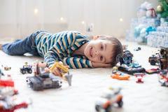 Piccolo bambino che gioca con i lotti dei giocattoli di plastica variopinti dell'interno Fotografia Stock