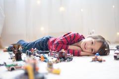 Piccolo bambino che gioca con i lotti dei giocattoli di plastica variopinti dell'interno Immagine Stock Libera da Diritti