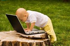 Piccolo bambino che gioca con il taccuino Fotografie Stock