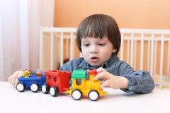 Piccolo bambino che gioca soffiatore di plastica Fotografie Stock Libere da Diritti