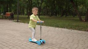 Piccolo bambino che impara guidare un motorino in un parco della città il giorno di estate soleggiato stock footage