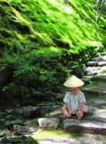 Piccolo bambino che indossa che un yukata tradizionale i giochi su ordinazione con la foresta lascia mentre si siede sopra i punt Fotografie Stock Libere da Diritti