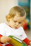 Piccolo bambino che legge un libro Fotografie Stock Libere da Diritti