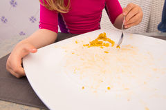 Piccolo bambino che mangia e che finisce grande piatto di paella Fotografia Stock Libera da Diritti