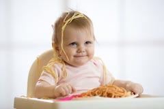 Piccolo bambino che mangia il suo pranzo e che fa un disordine fotografia stock libera da diritti
