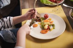 Piccolo bambino che mangia le verdure con la coltelleria Fotografia Stock