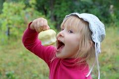 Piccolo bambino che mangia mela che lo tiene a disposizione fotografie stock libere da diritti