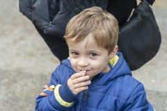 Piccolo bambino che mangia popcorn in un parco immagini stock