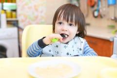 Piccolo bambino che mangia porridge Fotografie Stock Libere da Diritti
