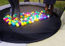 Piccolo bambino che salta sul trampolino nel campo da giuoco immagini stock