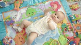 Piccolo bambino che si trova indietro sul tappeto variopinto con i giocattoli Ritratto infantile del ragazzo archivi video