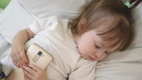Piccolo bambino che si trovano nell'ospedale sul letto e cadute addormentate con il telefono a disposizione stock footage