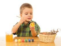 Piccolo bambino che vernicia le uova di Pasqua Fotografia Stock