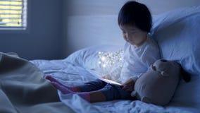 Piccolo bambino cinese asiatico che si siede sul letto con gli effetti speciali da ipad Fotografia Stock Libera da Diritti