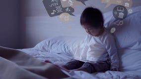 Piccolo bambino cinese asiatico che si siede sul letto con gli effetti speciali da ipad Fotografie Stock Libere da Diritti