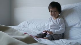 Piccolo bambino cinese asiatico che si siede sul letto con ipad Immagini Stock Libere da Diritti
