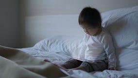 Piccolo bambino cinese asiatico che si siede sul letto con ipad Fotografie Stock